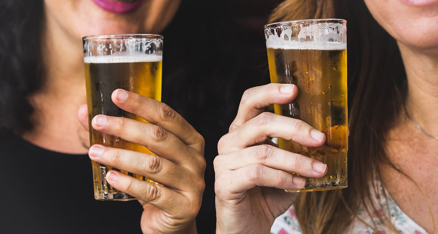 two women holding glasses of beer